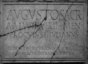 Augusto sacr(um) / AA(uli) Lucii A(uli) filii Men(enia) / Proculus et Iulianus / p(ecunia) s(ua) / dedicatione decurionibus et / Augustalibus cenam dederunt
